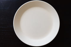 Empty white plate on black wooden table Royalty Free Stock Images