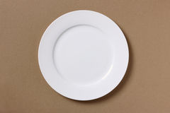 Empty white plate on brown background Royalty Free Stock Image