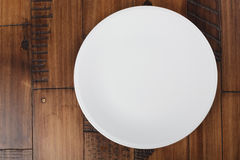 Empty white plate. On brown wooden table. Food background Royalty Free Stock Photo