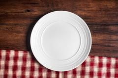 Empty white plate on a checkered red napkin on an old wooden brown background, top view. Image with copy space. Kitchen table with. A towel and a plate - top Royalty Free Stock Images