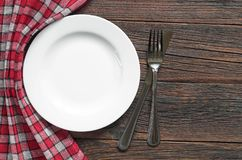 Plate and cutlery. Empty white plate and cutlery on dark wooden table, top view Royalty Free Stock Photography