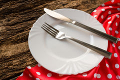 Empty white plate and cutlery on red napkin Stock Images