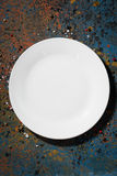 Empty white plate on a dark background, vertical, top view Stock Images
