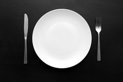 Empty white plate on dark wooden table. Empty white plate with fork and knife on dark wooden table Stock Photos