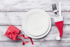 Empty white plate and decoration on wooden rustic table top view. Christmas table setting concept. Royalty Free Stock Image