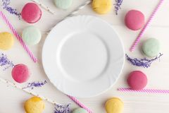 An empty, white plate, with a delicious dessert around, macaroons and tubes for a cocktail. Place for text. Festive Royalty Free Stock Photos