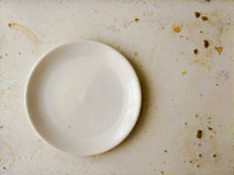 Empty white plate on dirty stained board. Attrition concept. Empty clean round white plate on dirty strained worn desk. Attrition concept. Hygiene illustration Stock Image