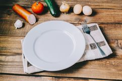 Empty White Plate. On home kitchen wooden table Royalty Free Stock Image