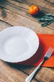 Empty White Plate. On the home wooden kitchen table Royalty Free Stock Photography