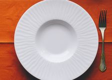 Empty White Plate. On the red kitchen table Stock Photography