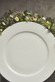 Empty white plate with flowers decorations Royalty Free Stock Image
