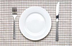 Empty white plate with fork and knife Royalty Free Stock Photography