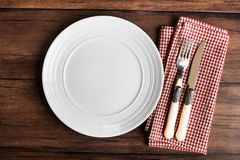 Empty white plate, fork and knife on a checkered red napkin on an old wooden brown background, top view. Image with copy space. Ki. Tchen table with a towel and stock image
