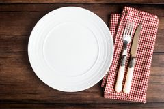 Empty white plate, fork and knife on a checkered red napkin on an old wooden brown background, top view. Image with copy space. Ki Stock Photography