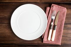 Empty white plate, fork and knife on a checkered red napkin on an old wooden brown background, top view. Image with copy space. Ki Royalty Free Stock Images