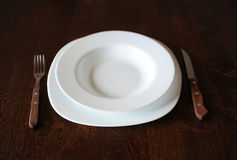 Empty white plate with a fork and knife on a dark wooden brown table Royalty Free Stock Image