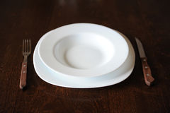 Empty white plate with a fork and knife on a dark wooden brown table Royalty Free Stock Photography
