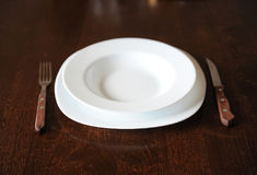 Empty white plate with a fork and knife on a dark wooden brown table Royalty Free Stock Photos