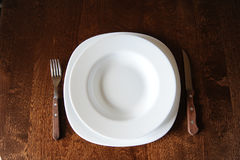 Empty white plate with a fork and knife on a dark wooden brown table Stock Photos