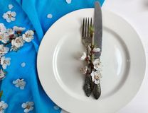 Empty white plate with a fork and knife on a white wooden surface. With a blue napkin and cherry blossoms Stock Images