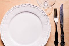 White plate fork knife and crystal glass on wooden table. Top view royalty free stock image