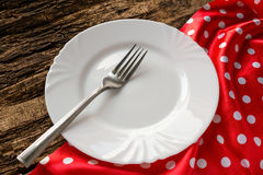Empty white plate with a fork on a red napkin Stock Image