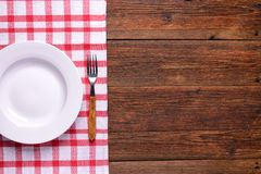 Empty white plate with fork on rustic wooden background Royalty Free Stock Image