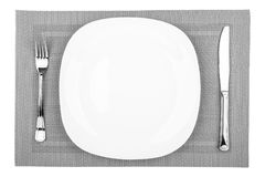 Empty White Plate. Fork, table knife and empty white plate on a placemat closeup, top view Royalty Free Stock Image