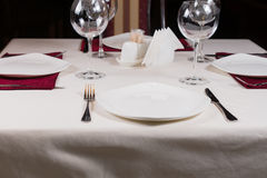 Empty white plate in a formal table setting. On a table set with a white tablecloth, wineglasses and cutlery Stock Photography