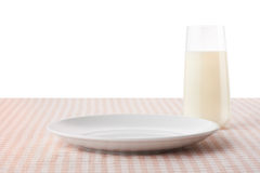 Empty white plate and glass of milk on checkered tablecloth Royalty Free Stock Photo