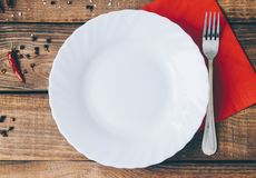 Empty White Plate. On the home wooden kitchen table Royalty Free Stock Image