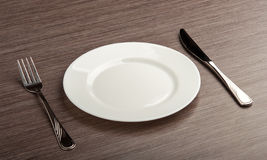 Empty white plate with knife and fork Stock Photography