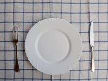 Empty white plate with knife and fork. In the background, a blue checkered napkin Stock Image