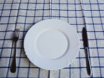 Empty white plate with knife and fork. In the background, a blue checkered napkin Royalty Free Stock Photo