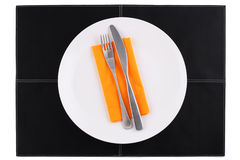 Empty white plate with knife and fork on black Stock Images