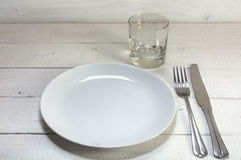 Empty white plate with knife, fork and drinking glass on a white Royalty Free Stock Image