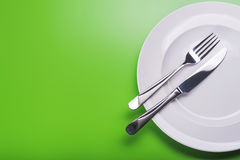 Plate with knife and fork. Empty white plate with knife and fork on green background. view from top royalty free stock photos