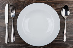 Empty white plate, knife, fork and spoon on table Royalty Free Stock Image