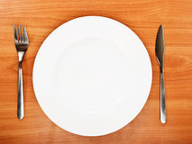 Empty white plate with knife and fork. On a  wooden table Royalty Free Stock Photos
