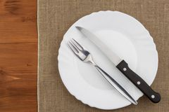 Empty white plate with knife and fork on a wooden table. Waiting for food. Home dining. Directly above view of table setting. Royalty Free Stock Photography