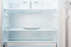 Empty white plate in open empty refrigerator Royalty Free Stock Photos