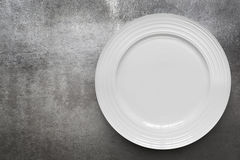 Empty White Plate over Gray Slate Top View. Empty white plate over gray slate. Top view, with copy space Stock Photo