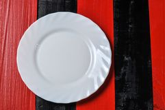 Empty white plate on red and black wooden background. Setting domestic nobody utensil dining metal dish table restaurant clean dinner meal fork studio lunch stock image