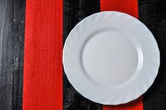 Empty white plate on red and black wooden background. Setting domestic nobody utensil dining metal dish table restaurant clean dinner meal fork studio lunch royalty free stock images