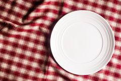 Empty white plate on a red checkered napkin on an old wooden brown background, top view. Image with copy space. Kitchen table with. A towel and a plate - top stock photography