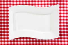 Empty white plate on red napkin or tablecloth. Top view. Template for your food and product display montage. Concept food. Copy