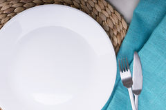 Empty White Plate. Round clean empty white plate on wooden mat Stock Image