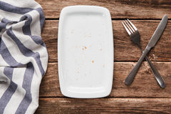 Empty white plate on rustic wooden table, top view. Food background. Meal is finished. Empty white rectangular plate on rustic wooden background, flat lay Royalty Free Stock Image