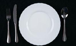 Empty white plate with silver fork, knife and spoon isolated on black background. Dinner place setting. Top view. Stock Photo
