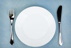 Empty white plate with silverware on wooden table. Empty white plate with silverware on blue wooden table Royalty Free Stock Photography